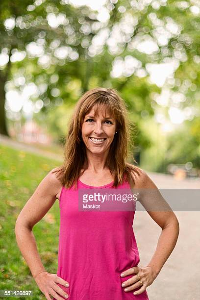 Portrait of happy fit mature woman standing with hands on hips at park