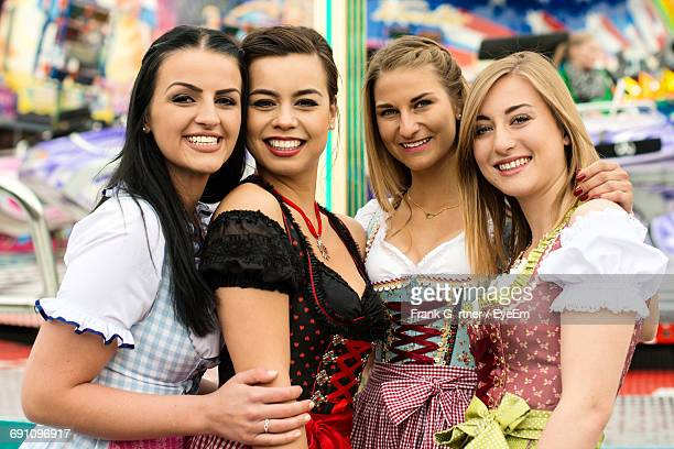 Portrait Of Happy Friends At Amusement Park During Oktoberfest