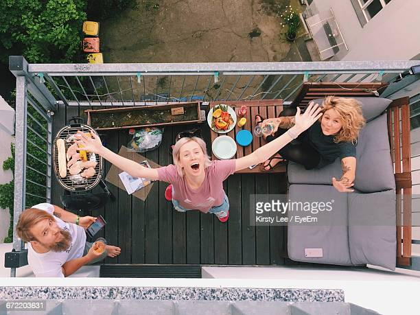 portrait of happy friends having barbeque party in balcony - balcony stock pictures, royalty-free photos & images