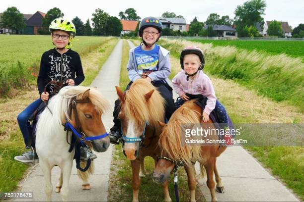 Portrait Of Happy Friends Riding On Pony On Footpath Amidst Grassy Field