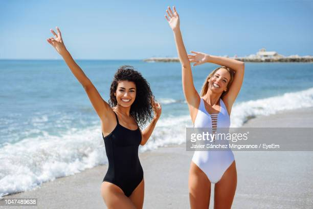 portrait of happy friends with arms raised standing at beach during sunny day - swimwear stock pictures, royalty-free photos & images