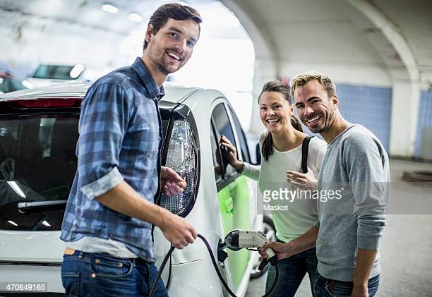 portrait of happy friends with man charging electric car at gas station - elektroauto stock-fotos und bilder