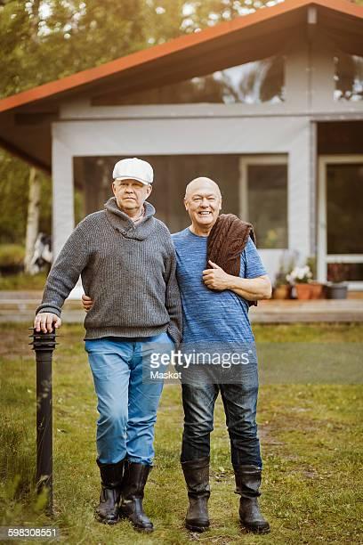 portrait of happy gay couple standing at yard - paal stockfoto's en -beelden