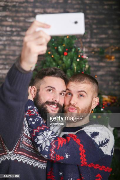 Portrait of happy gay couple taking selfie with smartphone at Christmas time at home