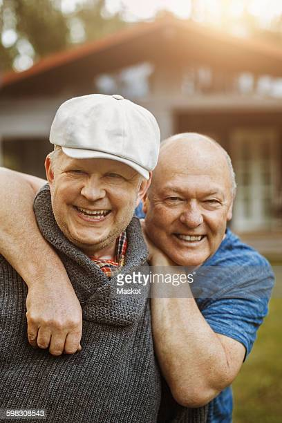 Portrait of happy gay man leaning on partners shoulders at yard