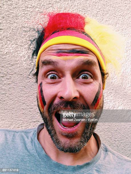 portrait of happy german soccer fan against wall - german culture stock pictures, royalty-free photos & images