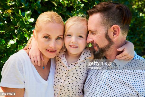portrait of happy girl between her parents - femme entre deux hommes photos et images de collection