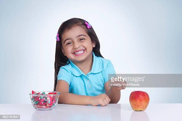 Portrait of happy girl choosing between apple and sweet food against blue background