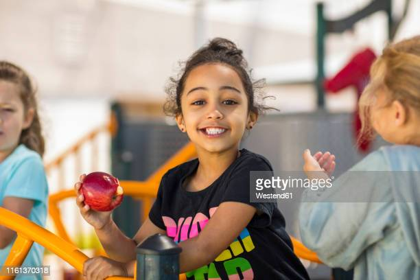 portrait of happy girl eating an apple in kindergarten - children only stock pictures, royalty-free photos & images