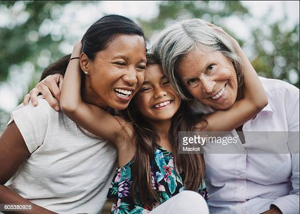 Portrait of happy girl embracing mother and grandmother at yard