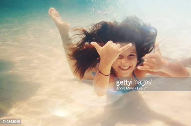 Portrait Of Happy Girl Gesturing Shaka Sign While Swimming In Pool