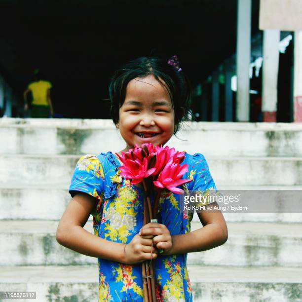 portrait of happy girl holding flowers - ko ko htike aung stock pictures, royalty-free photos & images