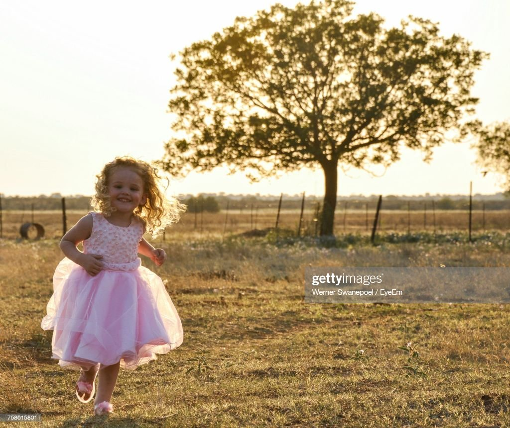 Portrait Of Happy Girl In Dress Running On Grassy Field Against Clear Sky : Stock Photo