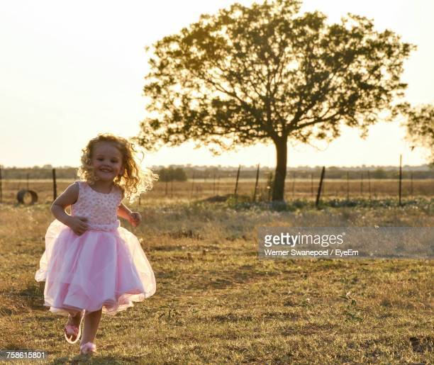 Portrait Of Happy Girl In Dress Running On Grassy Field Against Clear Sky