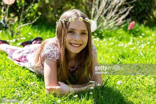 portrait of happy girl lying on meadow in garden - mädchen stock-fotos und bilder