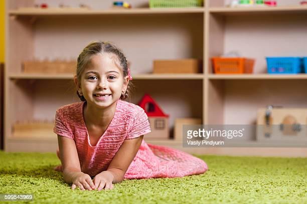 Portrait of happy girl lying on rug in classroom
