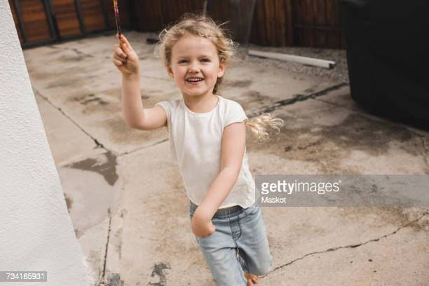 portrait of happy girl playing with magic wand outside house - zaubertrick stock-fotos und bilder