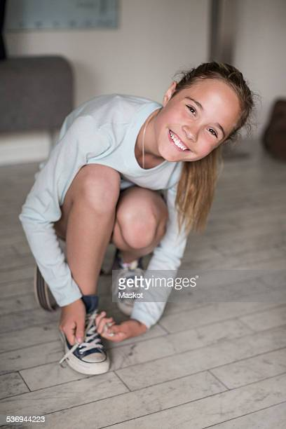 Portrait of happy girl putting on canvas shoe at home