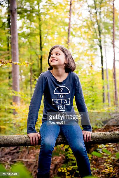 Portrait of happy girl sitting on a pole in the forest
