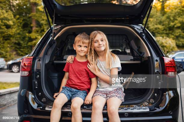 portrait of happy girl sitting with brother in car trunk - boot stock pictures, royalty-free photos & images