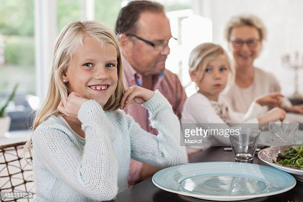 Portrait of happy girl sitting with family at dining table