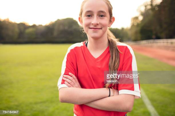 portrait of happy girl standing with arms crossed on soccer field - fußballtrikot stock-fotos und bilder