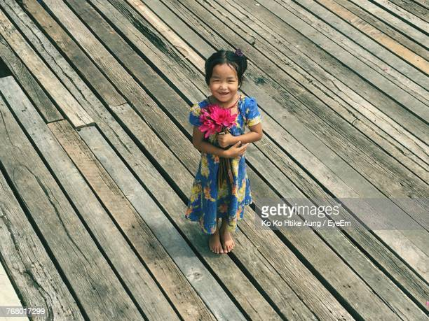 portrait of happy girl with pink flowers standing on wooden floor - ko ko htike aung stock pictures, royalty-free photos & images