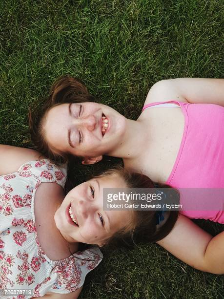 Portrait Of Happy Girl With Sister Lying Down On Grassy Field