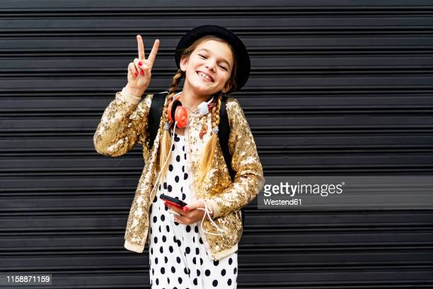portrait of happy girl with smartphone wearing hat and golden sequin jacket showing victory sign - gold jacket stock pictures, royalty-free photos & images