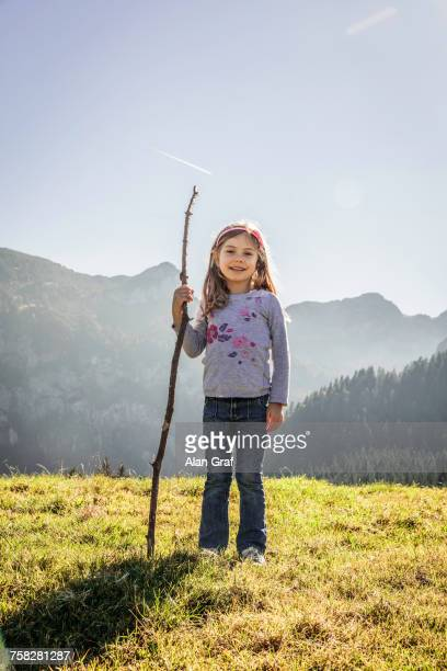 Portrait of happy girl with walking stick in sunlit mountain landscape, Bavaria, Germany