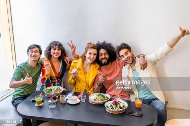 portrait of happy group of friends in a restaurant - cinq personnes photos et images de collection