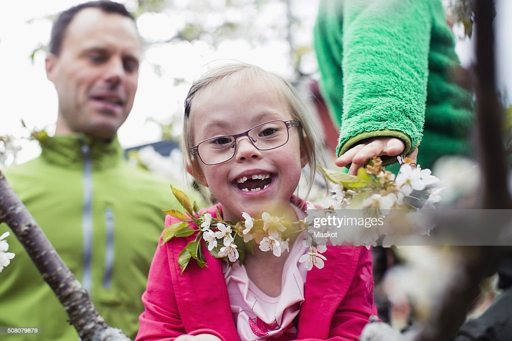 Portrait of happy handicapped girl with father and brother in yard : Stock Photo