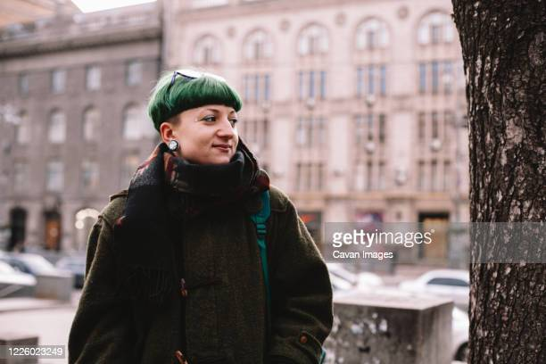 portrait of happy hipster woman standing on street in city - gender fluid stock pictures, royalty-free photos & images