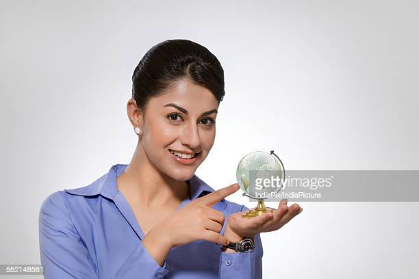 Portrait of happy Indian businesswoman holding crystal globe against gray background
