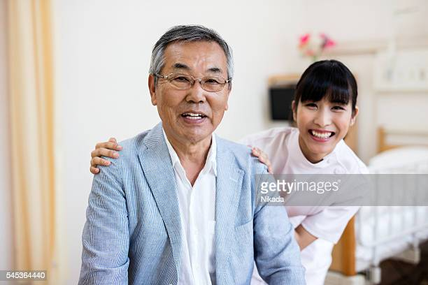 Portrait of happy japanese senior man with nurse in hospital