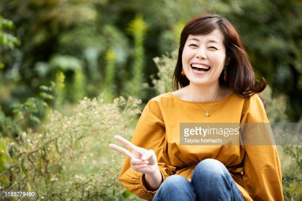 portrait of happy japanese woman - 中年 ストックフォトと画像