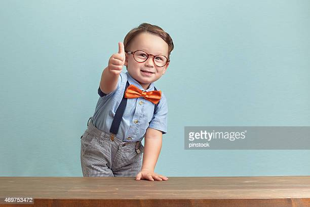 Portrait of happy little boy giving you thumbs up