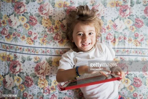 Portrait of happy little boy lying on bed with digital tablet