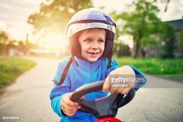 Portrait of happy little boy riding a fast go-kart.