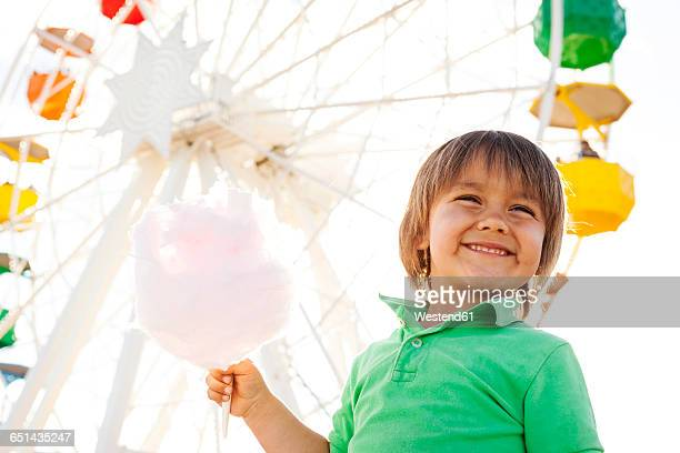 Portrait of happy little boy with cotton candy in front of big wheel