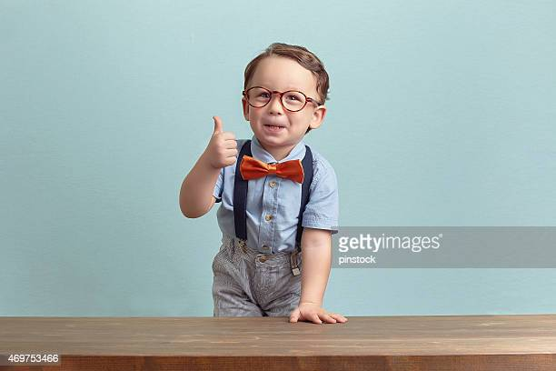 Portrait of happy little boy with glasses giving thumbs up