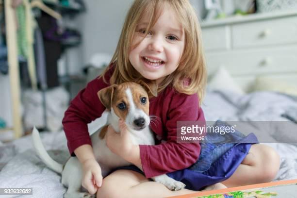 portrait of happy little girl crouching on bed with jack russel terrier puppy - 2 3 jaar stockfoto's en -beelden