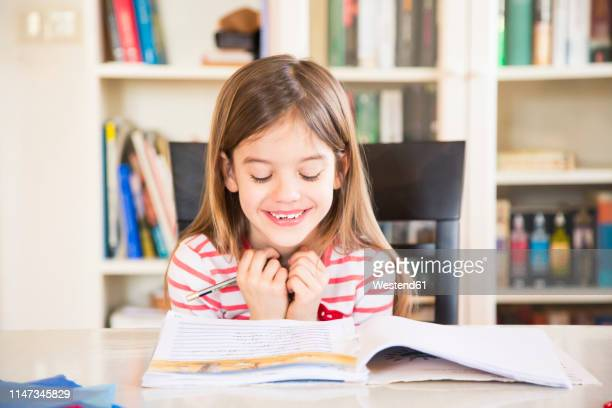 portrait of happy little girl doing homework - workbook stock photos and pictures
