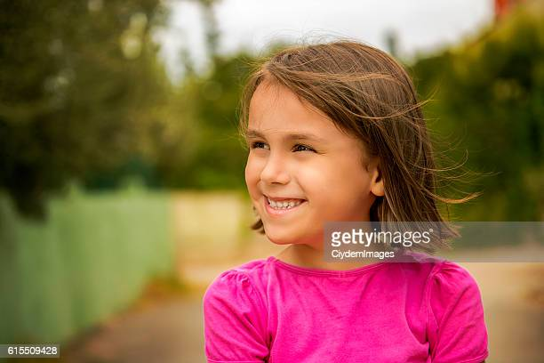 Portrait of happy little girl laughing against nature