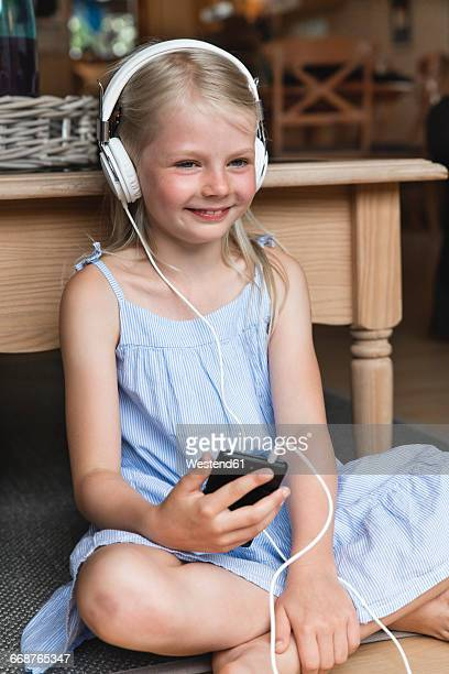 Portrait of happy little girl listening music with headphones and smartphone