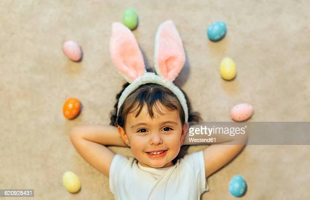 Portrait of happy little girl lying on the floor between Easter eggs