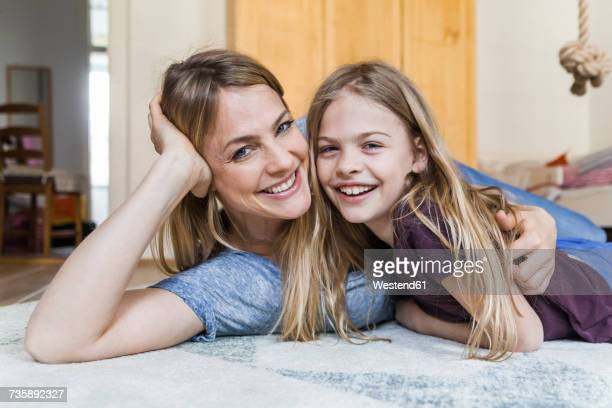 Portrait of happy little girl lying on the floor with her mother