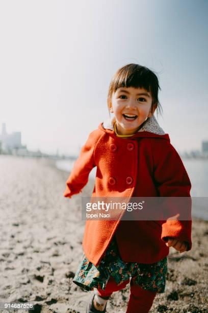 Portrait of happy little girl on beach in winter, Tokyo
