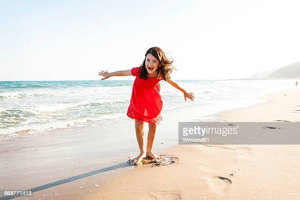 Portrait of happy little girl playing on the beach at seafront