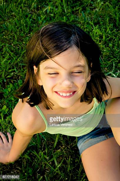 Portrait of happy little girl sitting on a meadow